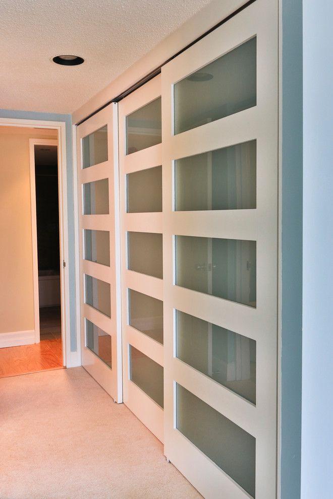 botanica white and glass sliding closet doors modernize this master bedroom  closet OENHBMR
