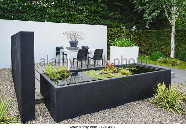 garden with modern garden furniture and trendy pond - stock image BNNASRF