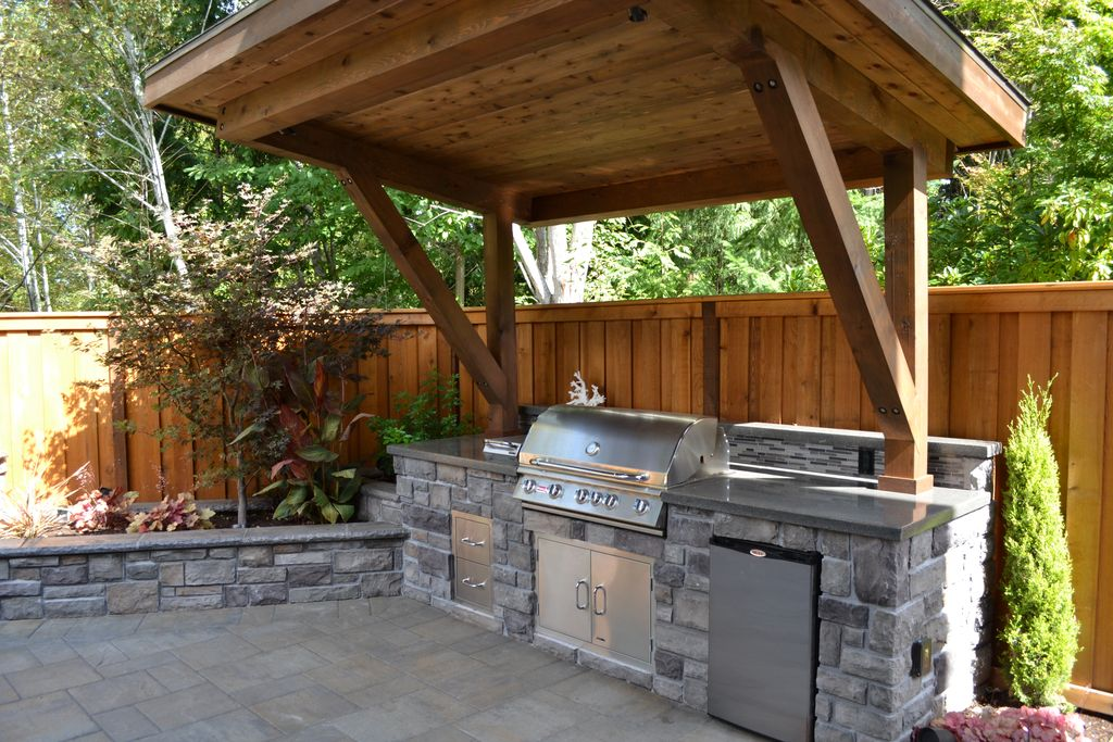 rustic patio with polished concrete, outdoor kitchen, raised beds, stacked  stone, fence UTDEMWZ