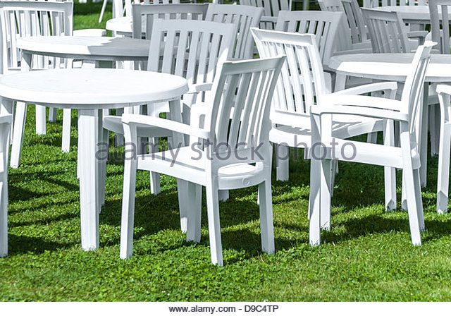 white plastic garden furniture on a lawn. - stock image NWVGTFF