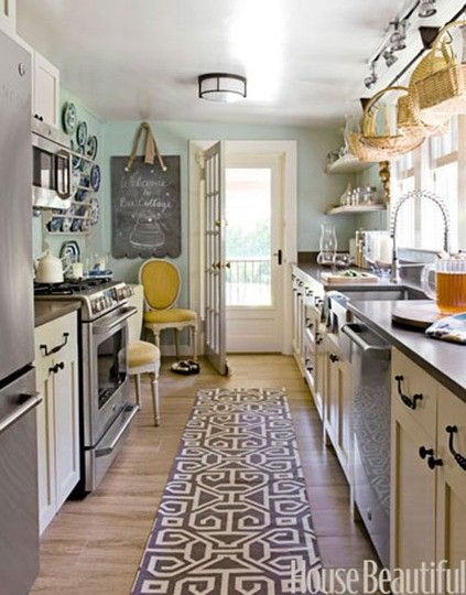 Galley kitchen with cream cabinets and blue wall @elise Anderson