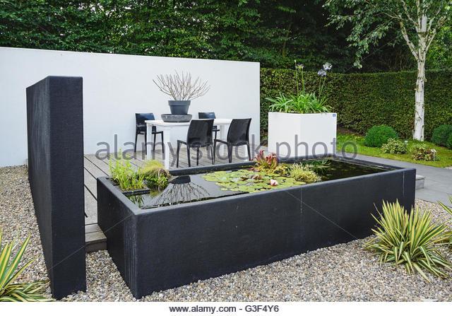 garden with modern garden furniture and trendy pond - stock image BNNASRF