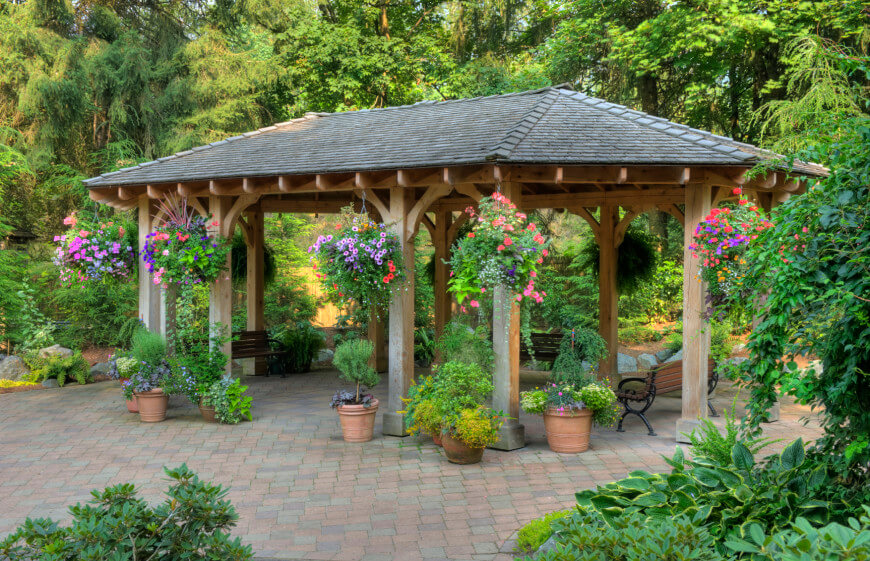 this patio gazebo houses a few benches and a number of potted plants. UAHSQXW