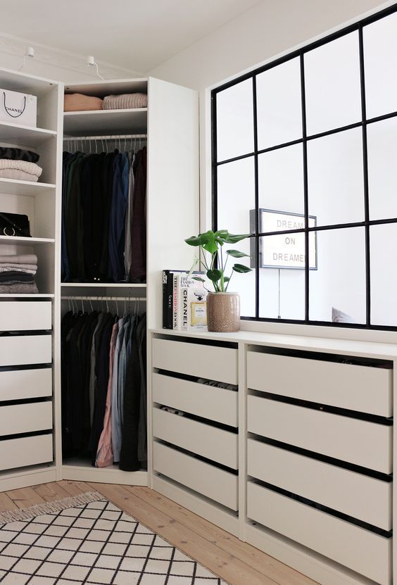 a comfy modern walk in closet with a large window and cabinets with