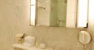 Elegant bathroom features hollywood style vanity mirror over white .