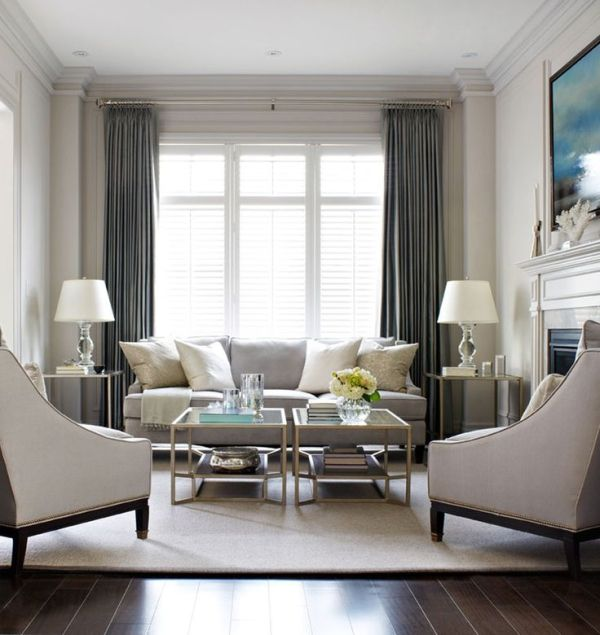 Elegant living room, with light grey sofa and arm chairs with .