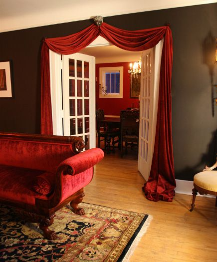 A red velvet sofa and matching swag over the French doors add .