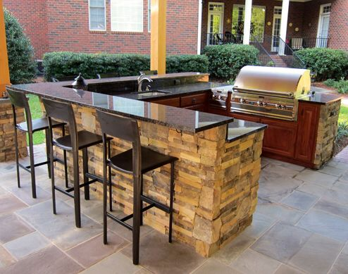 U shape outdoor kitchen island with bar top and pergola built over .
